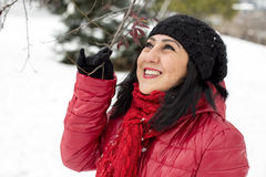 Black haired Turkish women looking at branches on a snowy day Royalty Free Stock Photo