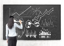 Black haired woman drawing a graph on a chalkboard Stock Photos