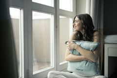 Black Haired Woman Hugging Gray Pillow Near Glass-panel Window Stock Images
