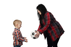 Black haired woman offers a soccer ball to small boy Stock Photo