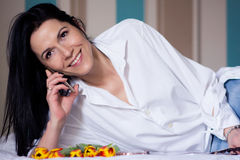 Black haired young woman in her bed in the morning Stock Image