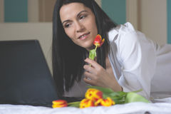 Black haired young woman in her bed in the morning Stock Photos