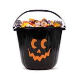 Black Halloween Jack o Lantern candy collector over white. Black Halloween Jack o Lantern candy collector filled with candy over a white background Royalty Free Stock Images