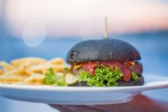 Black hamburger with French fries stock photos