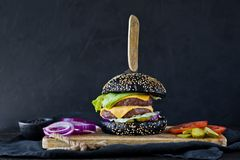 Black hamburger on a wooden chopping Board. Side view, black background, space for text. stock images