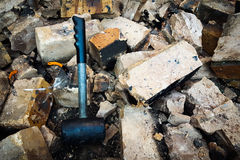 Black Hammer Breaks Down Wall. Black Rubber Hammer that demolish and break down brick wall brown and concrete. Broken Pieces. Chunks of Bricks. Crumble down Stock Photography