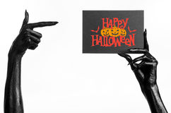 Black hand of death holding a paper card with the words Happy Halloween Stock Photo