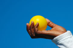 Black hand with yellow ball Stock Images