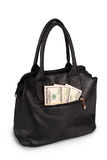 Black handbag full of money (Clipping path). Black handbag full of money isolated on white. Photo with clipping path Royalty Free Stock Images