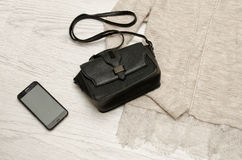 Black handbag and mobile phone on a beige cardigan. Wooden background. Fashionable concept, top view Stock Image