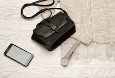 Black handbag, watch and mobile phone on a beige cardigan. Fashionable concept Stock Photos