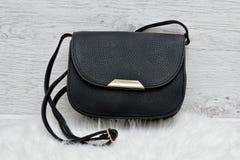 Black handbag on a white fur, light wooden background.  Stock Photography