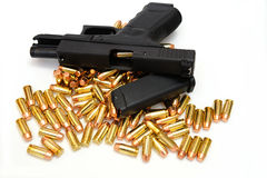 Black Handgun And Bullets. A semi automatic pistol with an extra 10 round magazine, and many .40 caliber brass cartridges. The weapon is locked open showing a Royalty Free Stock Photography