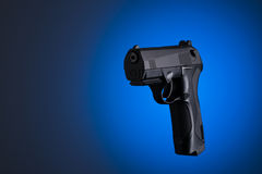 Black handgun isolated on blue background Royalty Free Stock Image