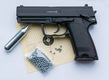 Black sports handgun with target, bullets and compressed air. Black handgun with target, bullets and compressed air for shooting sports - white background stock photography