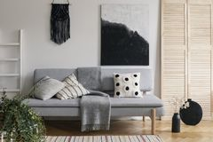 Black handmade macrame and fancy painting on white wall of sophisticated living room interior with grey fashionable couch with stock image
