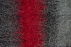 Black handmade woollen felt blanket with red stripe Stock Photos