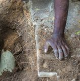 Black hands digging in the soil. Black hands doing manual labor digging in the soil image with copy space royalty free stock photos