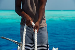 Black hands holding white rope Stock Photography