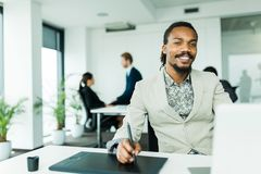 Black handsome graphics designer  with dreadlocks using digitize Stock Photos