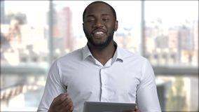 Black handsome manager using digital tablet. Afro-american business trainer holding computer tablet and talking to camera stock video footage