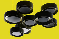 Black hanging lights from a yellow ceiling Royalty Free Stock Image