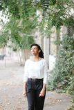 Black happy female person walking near building and green trees, wearing white blouse and black pants. Half american nigerian happy female person walking near stock photos