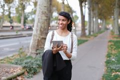 Black happy female student walking with tablet near street with trees. stock image