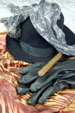 Black hat on a brown scarf with black leather gloves and a cigar on a marble table Royalty Free Stock Photos