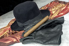 Black hat on a brown scarf with black leather gloves and a cigar on a marble table Royalty Free Stock Photography