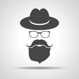 Black hat con i baffi, la barba ed i vetri isolati sull'sedere grige Fotografia Stock