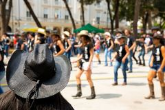 Black hat on flash mob backgroung. In city street stock photo