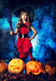 Black hat. Little girl in a costume of witch posing with pumpkins over dark background Stock Photos