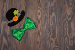 Black hat Saint Patricks green bow tie and leaf clover Stock Photos
