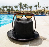 Black Hat with sunglasses around the pool at a resort Stock Photography