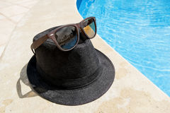 Black Hat with sunglasses around the pool at a resort Stock Images