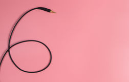 Black headphone jack on pink. Copy space Royalty Free Stock Photography