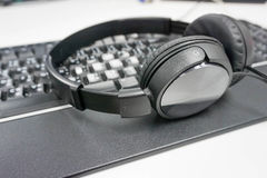 Black headphone on the keyboard. On the table Royalty Free Stock Photography