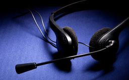 Black headphone with microphone. On dark blue background Royalty Free Stock Image