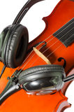 Black headphones on a classical wooden violin Stock Photos