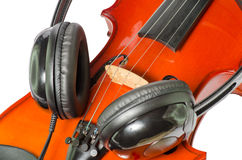 Black headphones on a classical wooden violin. Artistic conceptual close-up of a pair of black headphones on a brown classical wooden violin Royalty Free Stock Photo