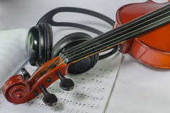 Black headphones on a classical wooden violin Royalty Free Stock Images