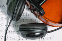 Black headphones on a classical wooden violin. Artistic conceptual close-up of a pair of black headphones on a brown classical wooden violin Stock Photos