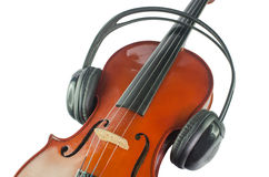 Black headphones on a classical wooden violin. Artistic conceptual close-up of a pair of black headphones on a brown classical wooden violin Stock Photography
