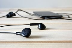 Black headphones connected to mobile phone on wooden table stock photos