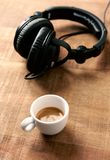 Black headphones and a cup of coffee on rustic wooden background. stock image