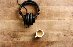 Black headphones and a cup of coffee on rustic wooden background. royalty free stock photos
