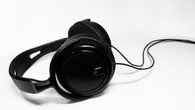 Black headphones over white. Isolated black headphones on white background with shadow Royalty Free Stock Photos