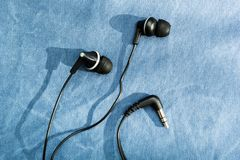 Black headphones with shadow on blue jeans background stock photography