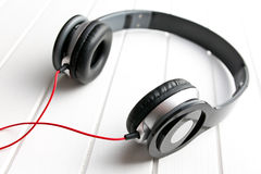 Black headphones. On white wooden table Stock Image